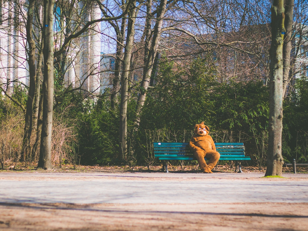 A person wearing a dog costume sitting on a bench in front of trees