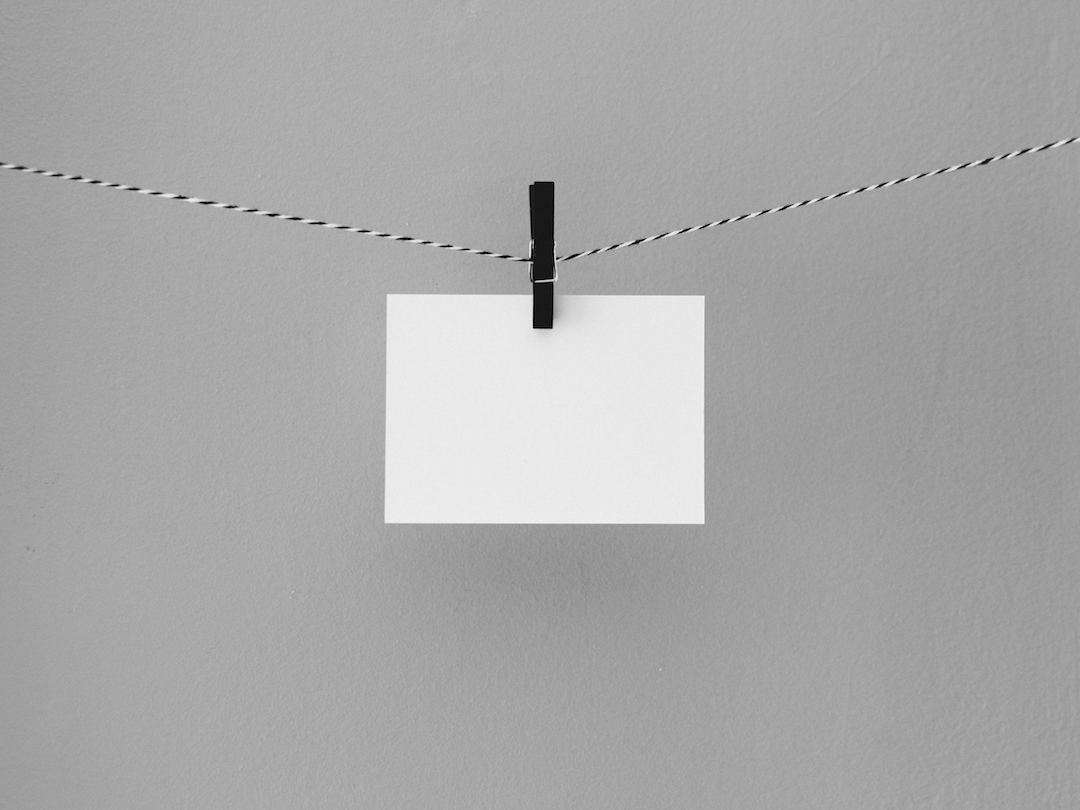 A simple white notecard being held by a clothespin