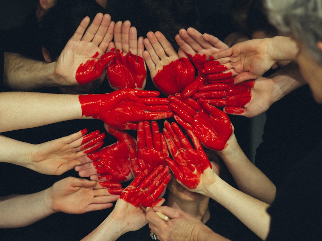 A group of hands together painted red to look like a heart