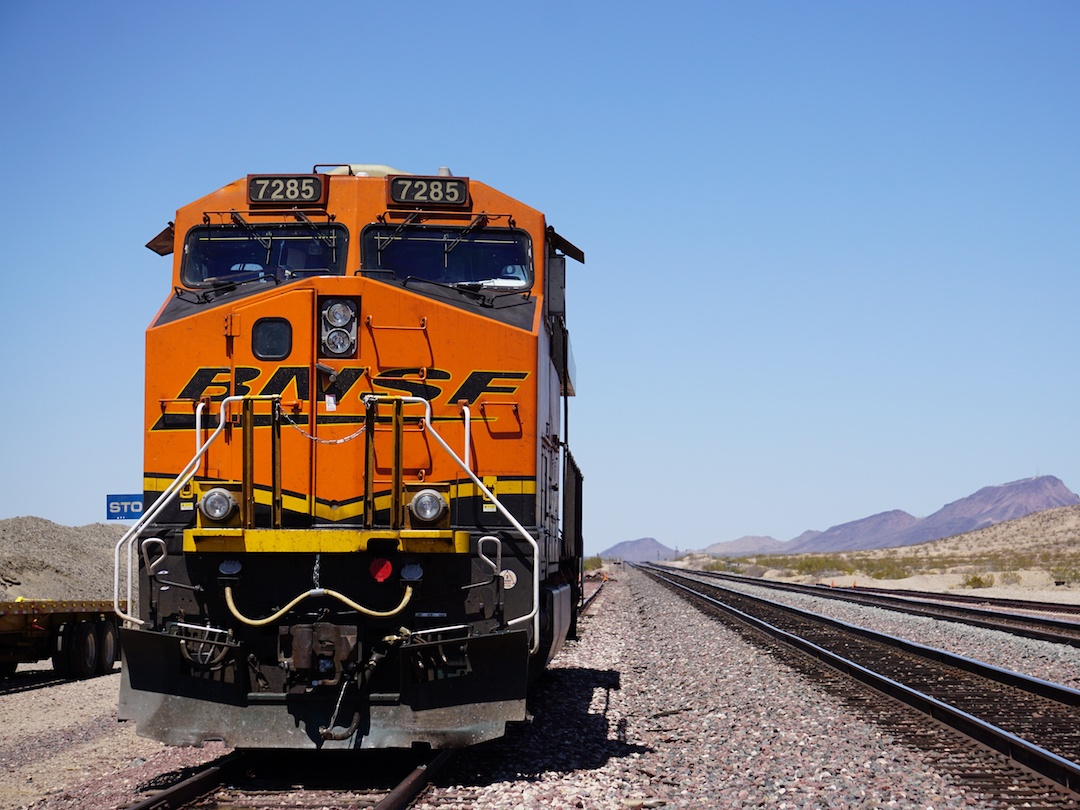 A large orange train gaining momentum on the tracks