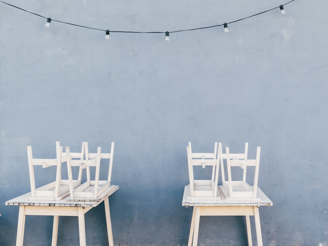 Two white tables with chairs stacked on top of them