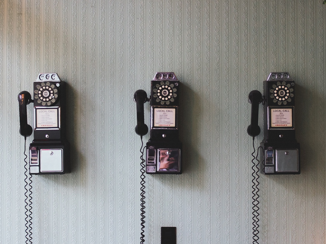 three black payphones on a white wall