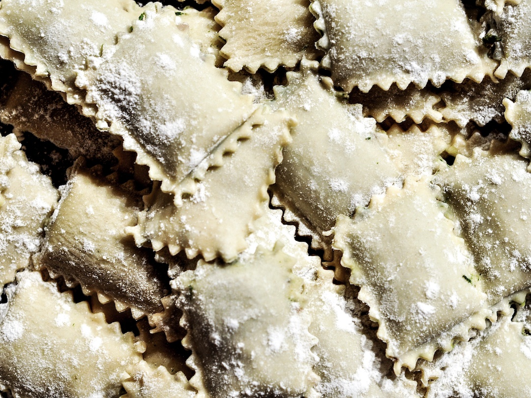 A pile of raw ravioli dusted with flour